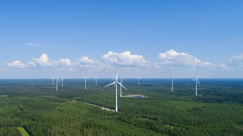 Wind power plant in the green field view and distant forest at summer evening. Concept of clean energy. stock photography