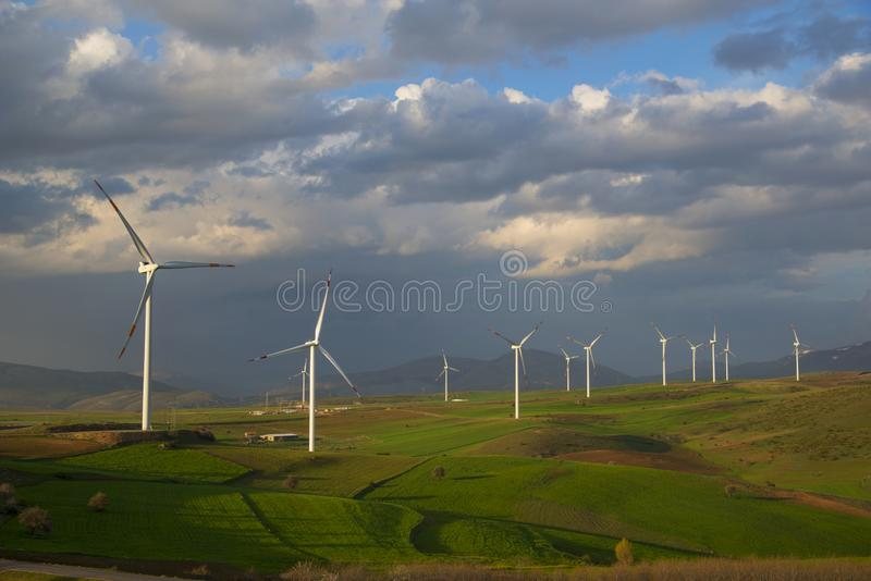 Wind power station among multicolored fields royalty free stock photos