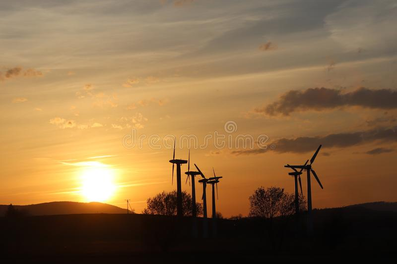Wind power station in sunset. Romantic evening and modern technologies of ecologically clean electricity. Protection of the enviro. Nment. Bright Future. An royalty free stock photo