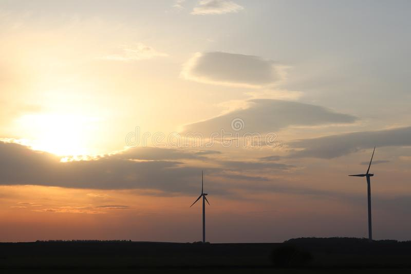 Wind power station in the sunset. Rotating blades of energy generators. Ecologically clean electricity. Modern technologies for t stock photography