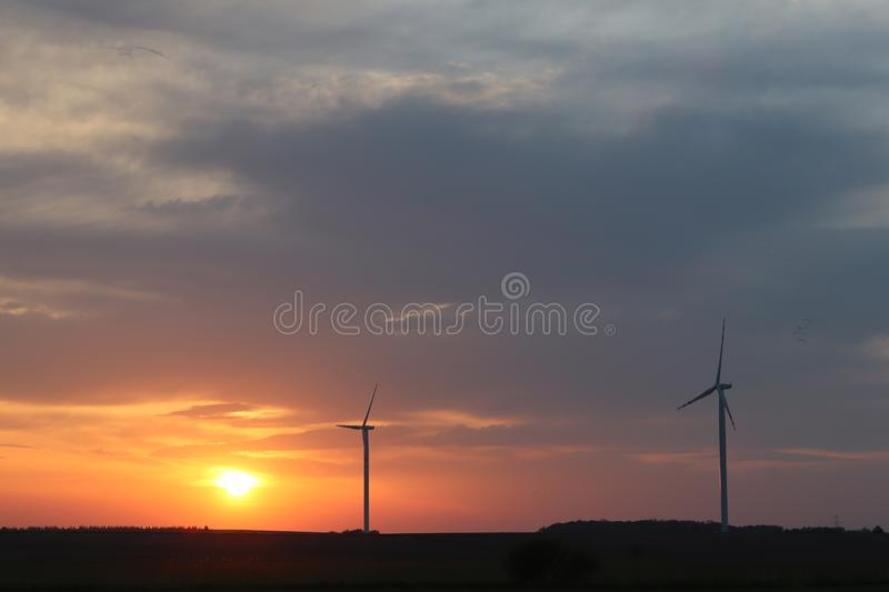 Wind power station in the sunset. Rotating blades of energy generators. Ecologically clean electricity. Modern technologies for t stock image