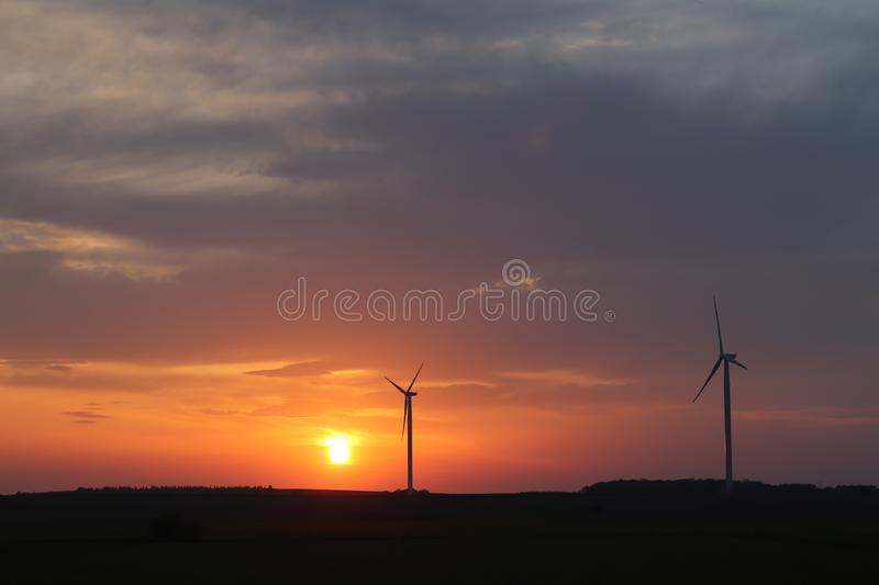 Wind power station in the sunset. Rotating blades of energy generators. Ecologically clean electricity. Modern technologies for t stock photo