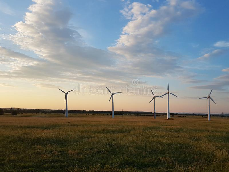 Wind power station in the sunset. Rotating blades of energy generators. Ecologically clean electricity. Modern technologies for t royalty free stock photo