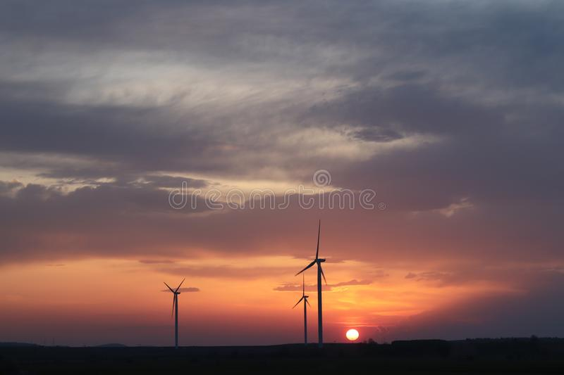 Wind power station in the sunset. Rotating blades of energy generators. Ecologically clean electricity. Modern technologies for t stock photos