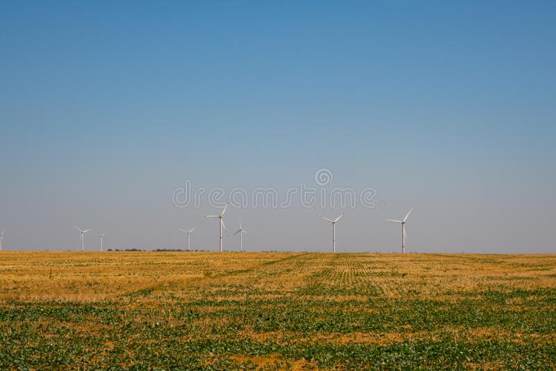 Wind power stations, turbine generators in the field against the blue sky royalty free stock photography