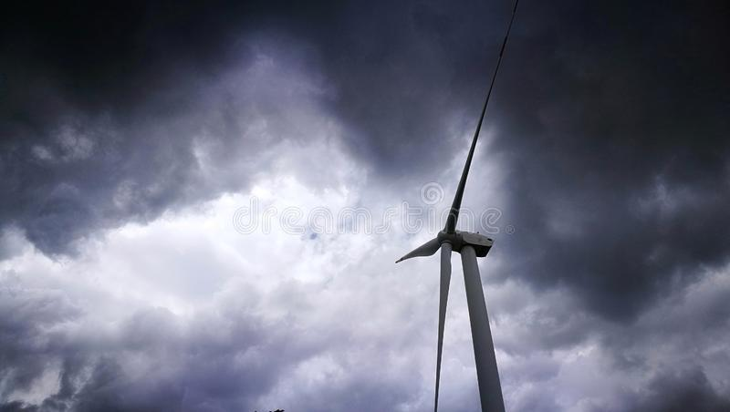 Wind power unit standing alone with glommy rain clouds surrounding royalty free stock photography
