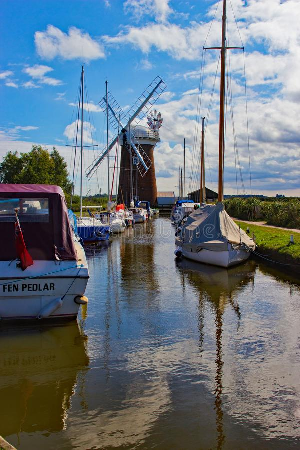 Wind pump and boats at Horsley Mere norfolk england royalty free stock photography