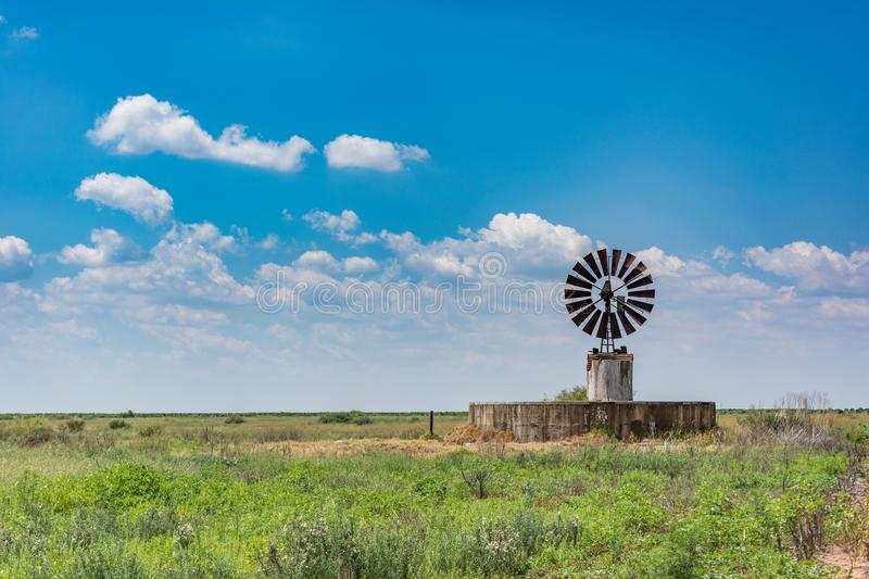 Wind pump on Freestate farm in South Africa. Wind pump and water reservoir on Freestate province farm in South Africa stock image