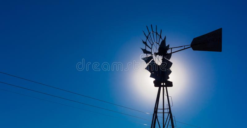 Wind pump windmill silhouette in the Karoo desert. Of South Africa royalty free stock images