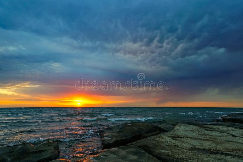 Dawn, a new day begins, the sea is stormy. The wind raises the waves and weaves the clouds royalty free stock image