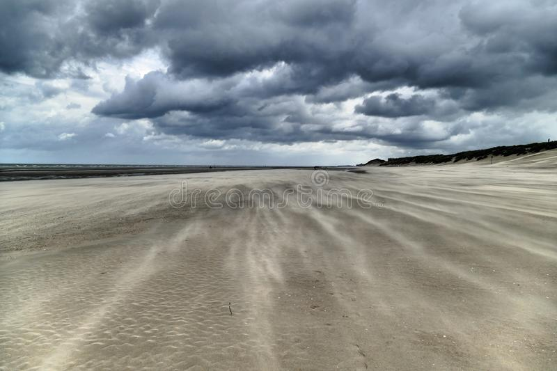 Impressive sand drifts and clouds during a hurricane at the Belgium coast royalty free stock photography