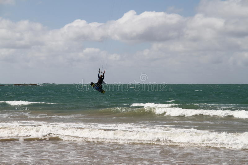 Wind surfer in air at the beach. Clouds and blue/green sea and a little surf stock photo