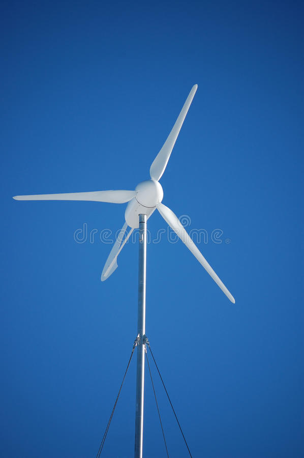 Wind Turbine. A white wind turbine against blue sky royalty free stock images