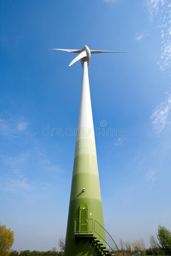 Wind turbine. Low angle view of a wind turbine against a blue sky stock images