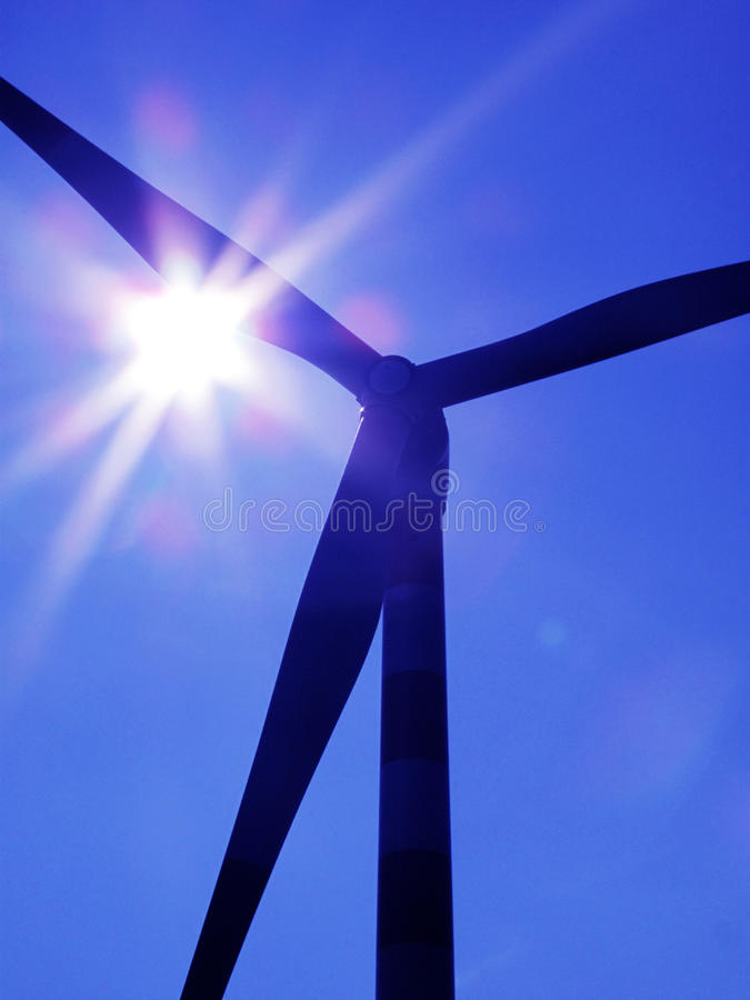 Wind turbine. Silhouette of a wind turbine against blue sky stock images