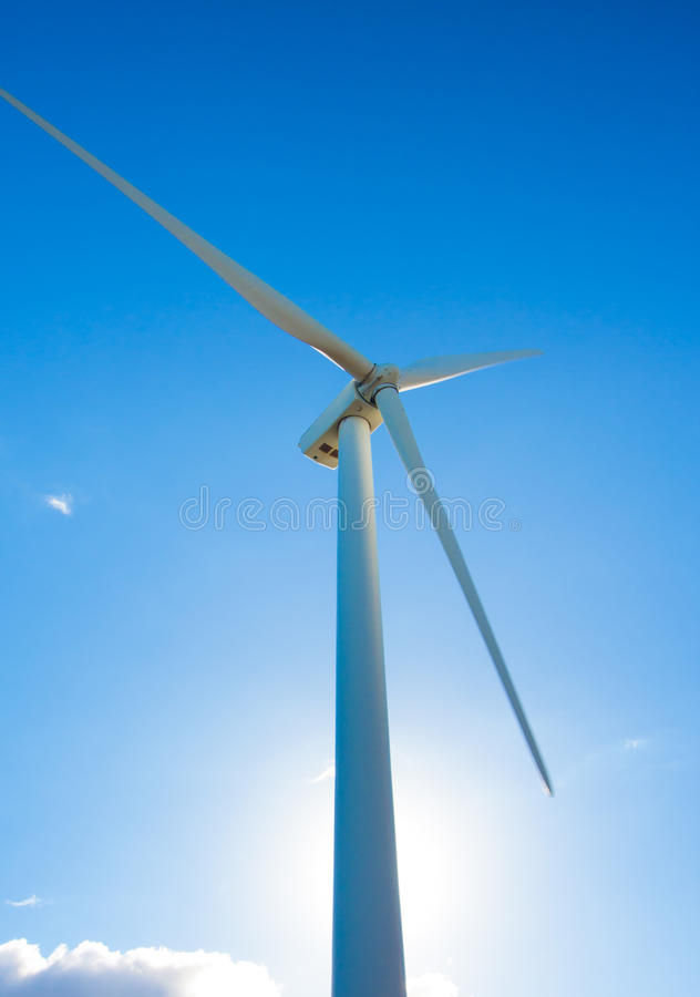 Wind Turbine. White Wind Turbine Generating Electricity on Blue Sky stock photos