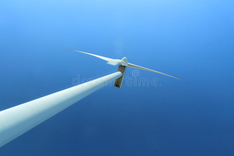Wind turbine against clear blue sky. Wind turbine power station against clear blue sky, alternative energy source stock photography