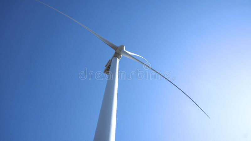 Wind turbine against clear sky on sunny day. Low angle view of wind turbine spinning against clear sunny sky royalty free stock image