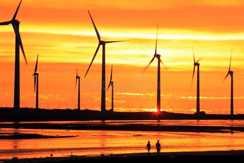 Wind turbine array silhouette under sunset. Wind turbine power generators standing on the sea coast with sunset stock image