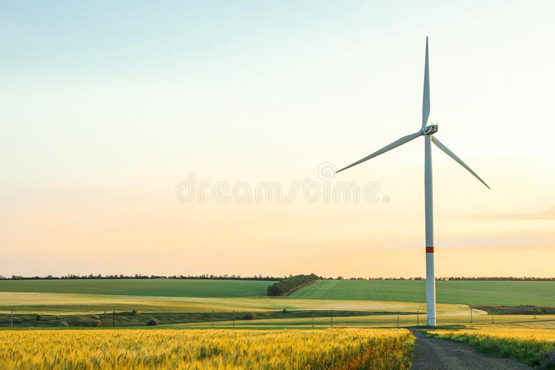 Wind turbine and beautiful fields at sunset royalty free stock image