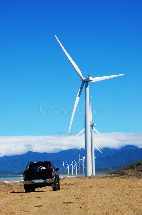 Wind turbine with a black pickup royalty free stock photography