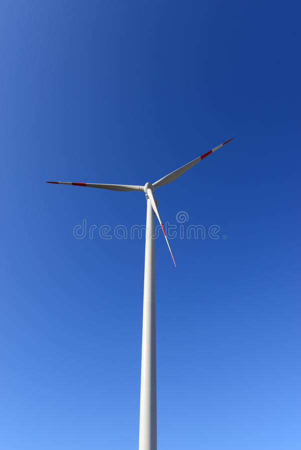 Wind turbine. On blue sky in background stock photography