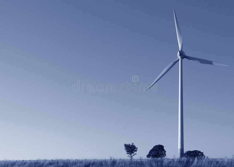 Wind turbine blue tint copyspace. Single wind power generator against clear sky, blue tint with plenty of copyspace royalty free stock photography