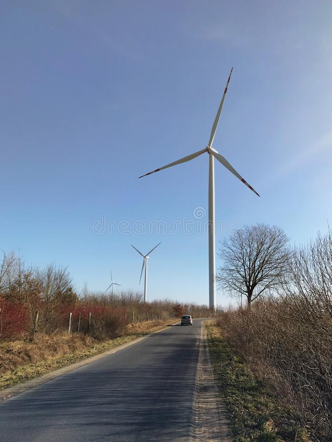 Wind turbine and car on spring day. A tall wind turbine and a car going along a rural road on spring day stock photos