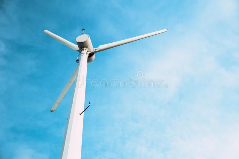 Wind turbine clean power energy on blue sky. With space for text royalty free stock photography