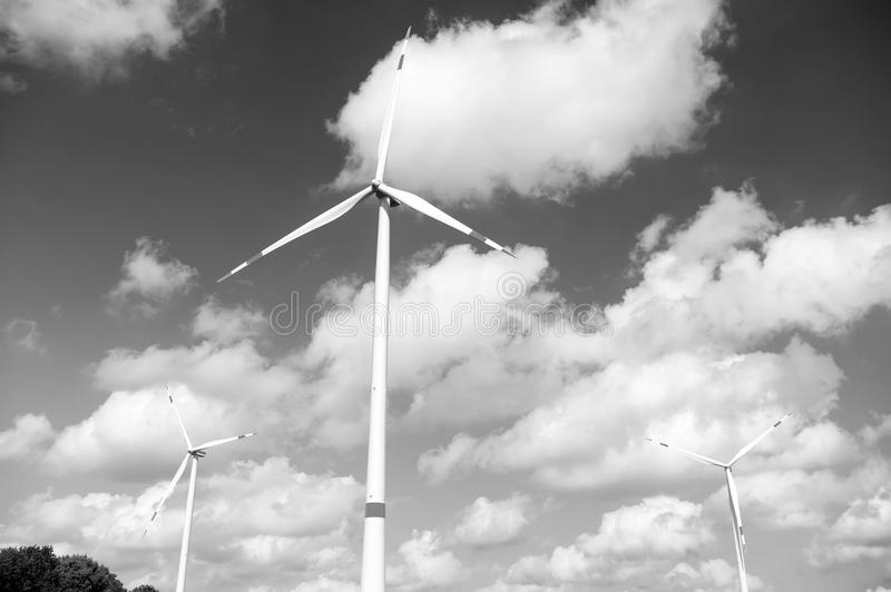Wind turbine on cloudy blue sky. Alternative energy and electricity source. Global warming. climate change and ecology. Eco power and green technology concept stock photos