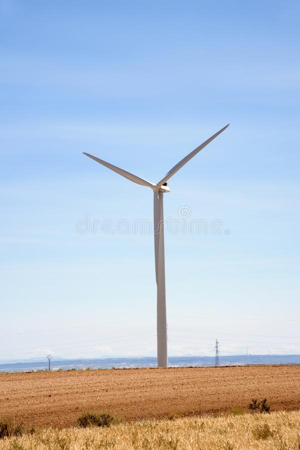 Wind turbine in a desert landscape. A view of a wind turbine in a desert landscape stock photo
