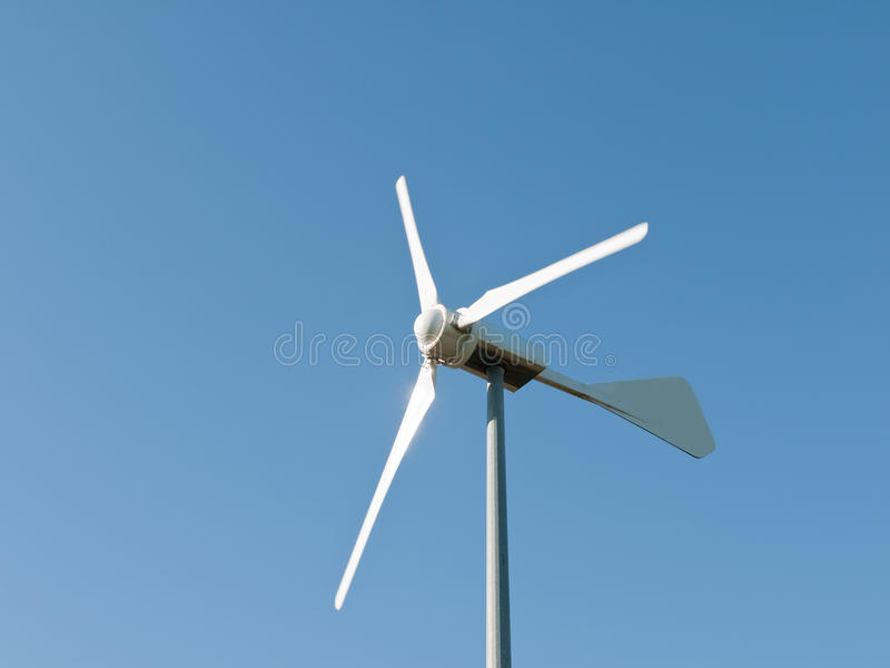 Wind turbine detail. Whirring small turbine, domestic scale, against bright blue sky stock images