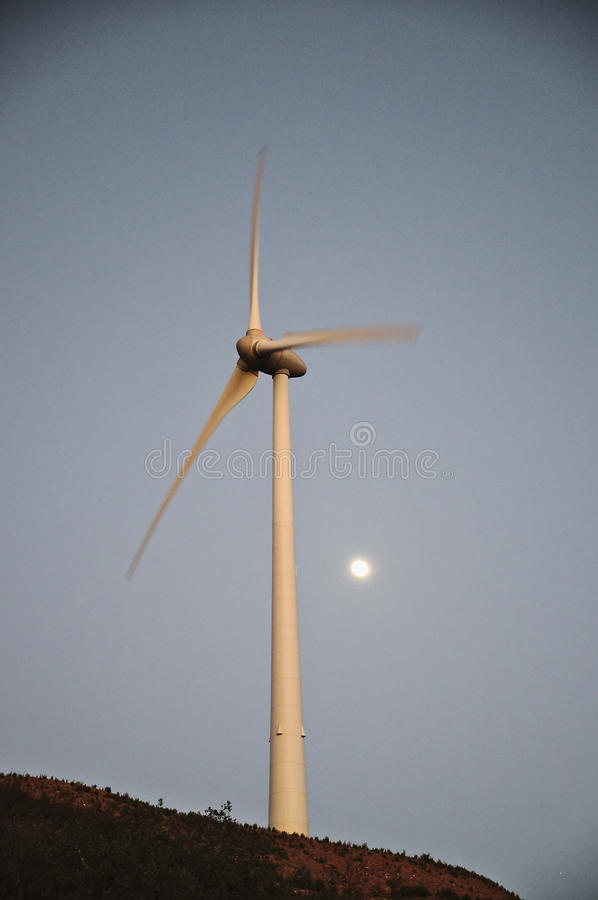 Wind turbine during dusk with moon behind. Clean energy industries royalty free stock photo