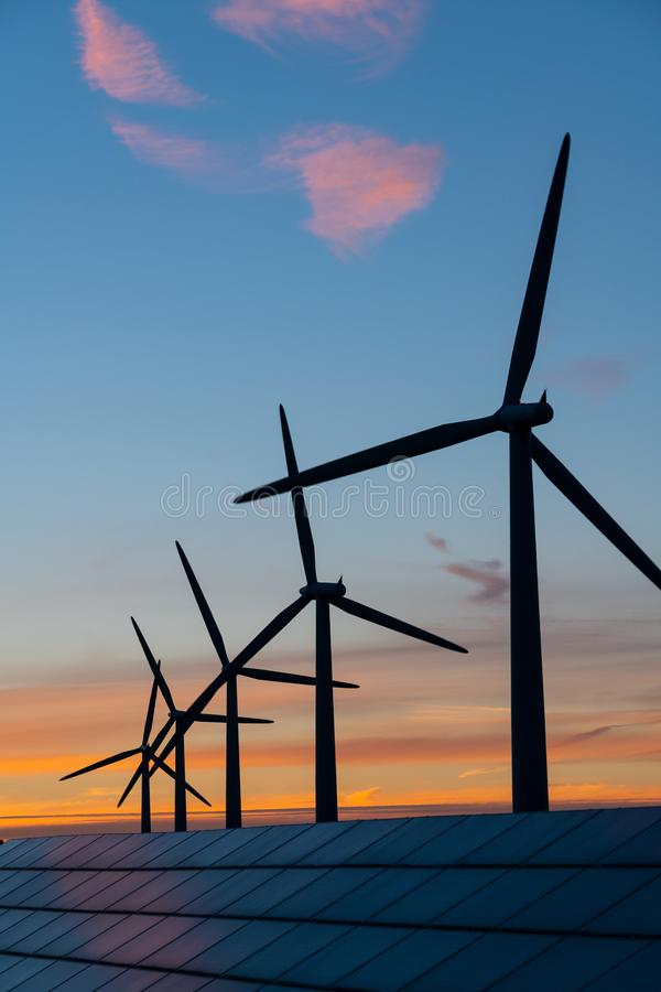 Wind turbine energy generaters on wind farm at sunset royalty free stock photography