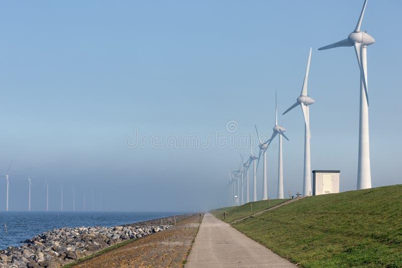 Wind turbines along Dutch dike in Flevoland near Urk. Wind turbine farm along Dutch dike in Flevoland near Urk stock photos