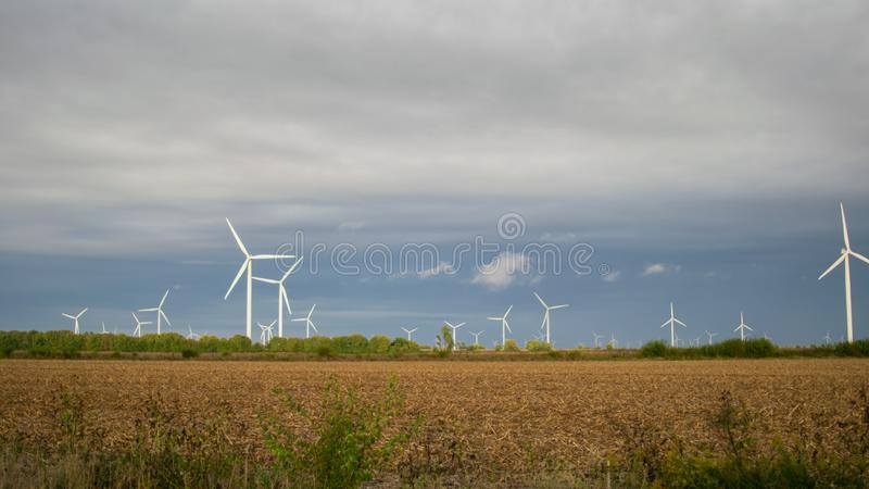Wind Turbine farm on a cloudy day in an open field. Wind Turbine farm on an autumn day in an open field royalty free stock image