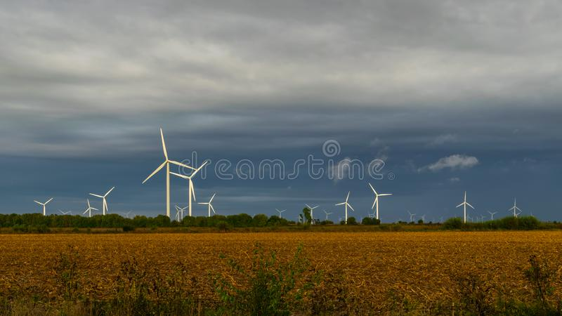 Wind Turbine Farm in an open field during a fall evening. Wind Turbine Farm in an open field with a storm on the horizon stock photography