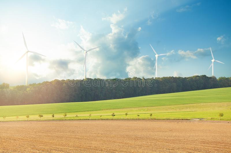 Wind turbine farm power generator in beautiful nature landscape for production of renewable green energy. Concept friendly stock photo