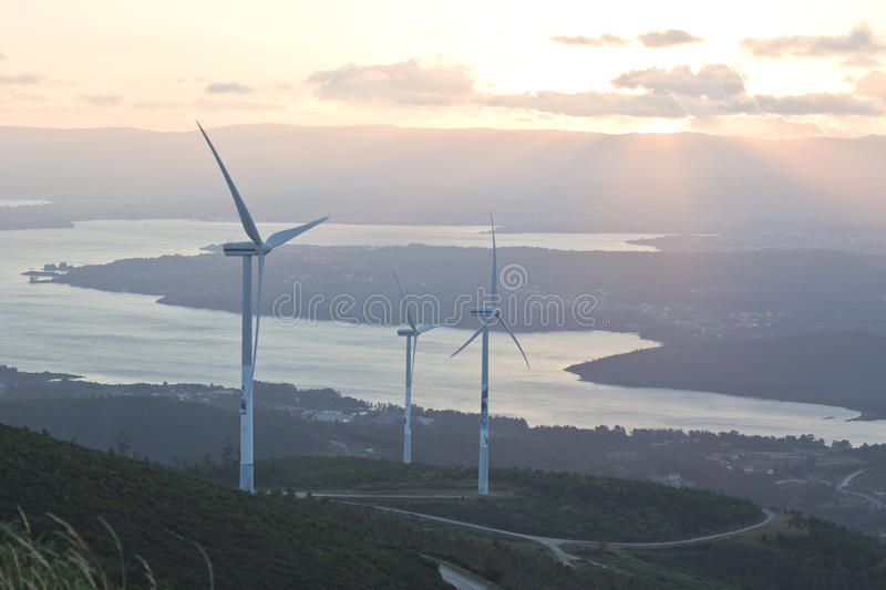 Wind turbine farm with rays of light at sunset royalty free stock photos