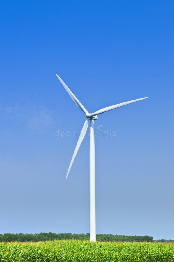 Wind turbine in field. Green alternative clean power wind turbine in field royalty free stock images