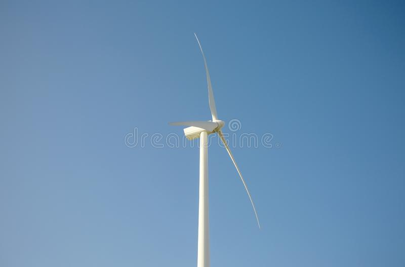 Wind turbine generating electricity over blue sky background royalty free stock image