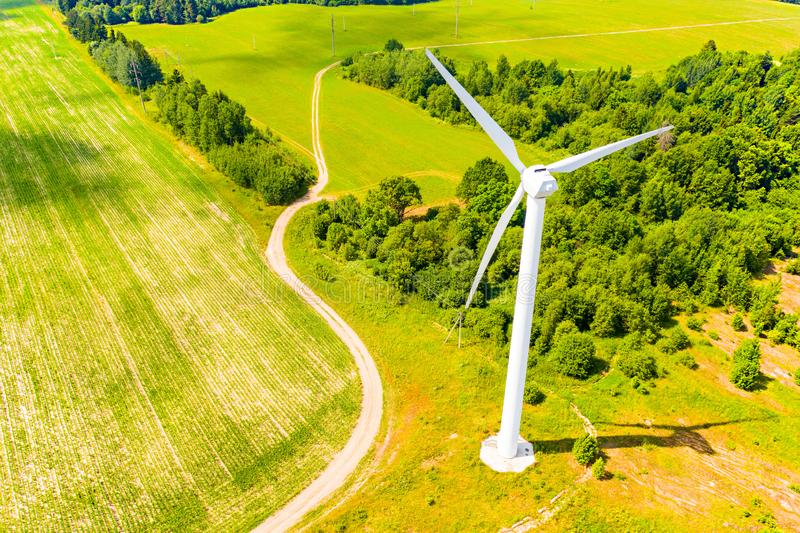 Wind turbine near green forest, aerial landscape. Producing energy in environmentally friendly way. Wind turbine near the green forest, aerial landscape royalty free stock images