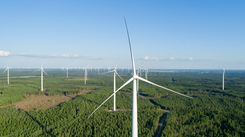 Wind turbine near green forest, beautiful aerial landscape with blue sky. Producing energy in environmentally friendly way. close royalty free stock photography