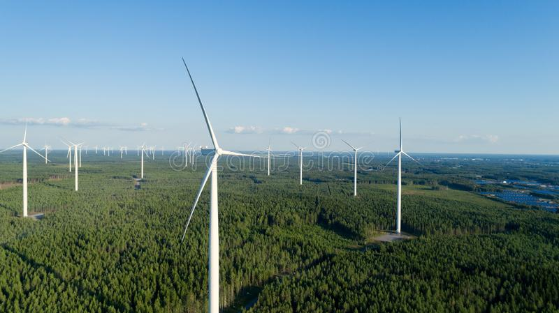 Wind turbine near green forest, beautiful aerial landscape with blue sky. Producing energy in environmentally friendly way. Close up royalty free stock photos