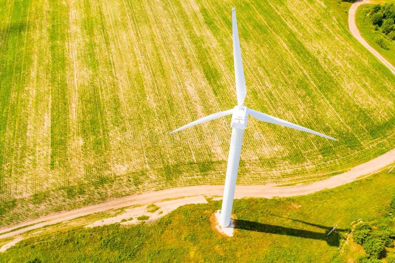Wind turbine near path in farmland, aerial landscape. Renewable energy concept royalty free stock photos