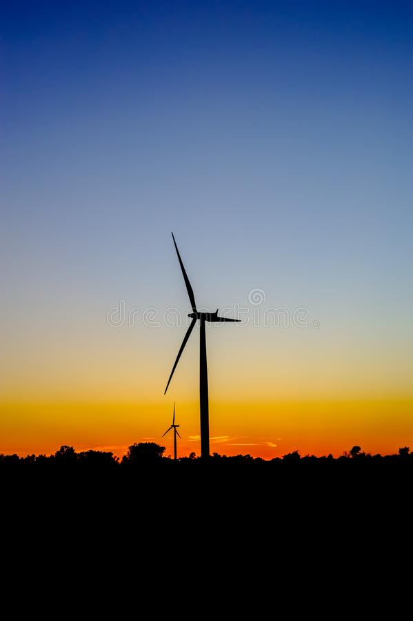 Wind turbine outline on red and blue sky stock photos