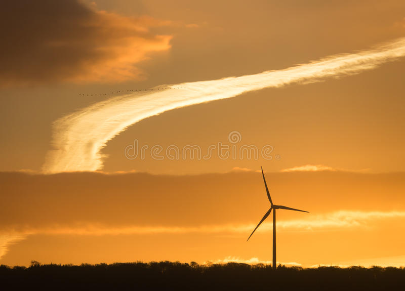 Wind Turbine Silhouette at Sunrise. Silhouette of Windturbine at Sunrise With Birds and Plane Contrail stock image
