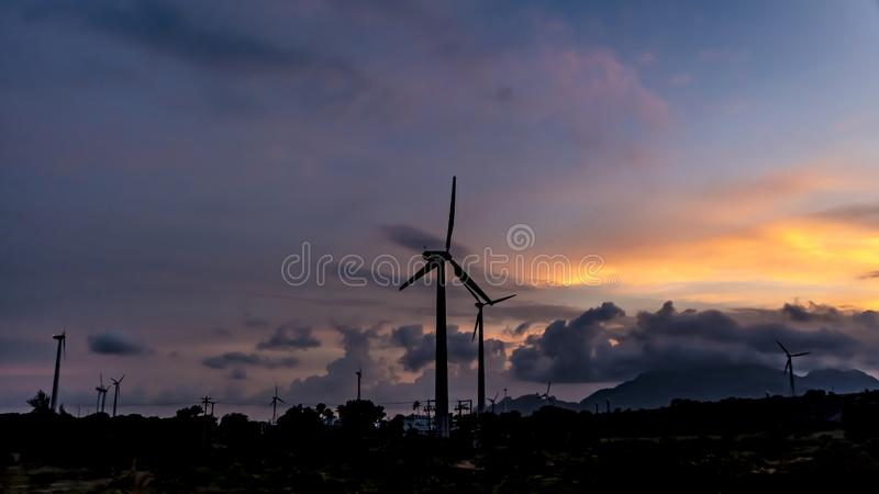 Wind Turbine silhouette on a sunset evening. A powerful picture displaying how true development can happen in an eco-friendly way. Picture showing palm trees and stock images