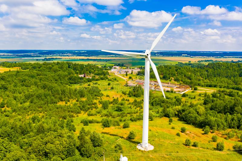 Wind turbine surrounded by green forest. Amazing landscape. Summer time. Alternative energy concept. Wind turbine surrounded by a green forest. Amazing landscape stock images