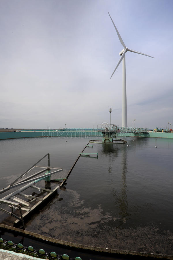 Wind Turbine and Waste Water Treatment. Wind turbine used to help power a waste water (sewage) treatment plant. Copy space royalty free stock image
